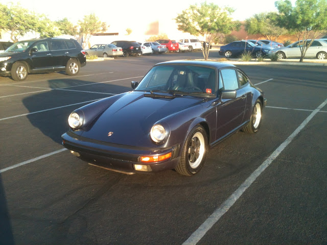 Front 3/4 view of purple 1986-1989 Porsche 911 parked in parking lot