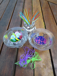 brightly coloured materials for bobbin huggers. pots of beads, buttons, elastic