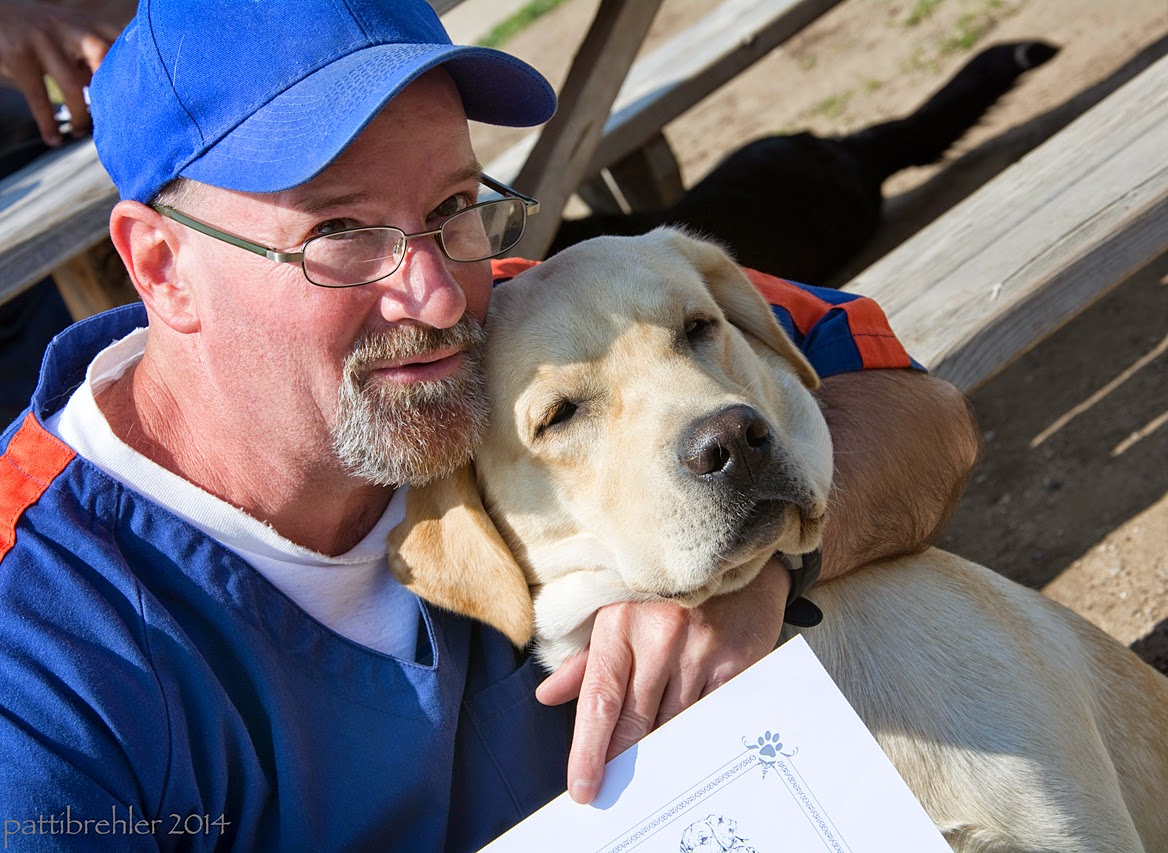 A close head and shoulders shot of the man dressed in a prison blue shirt and blue ball cap and glasses, with his left arm wrapped around the neck of the young yellow lab. The dog is pressed against the man's cheek.