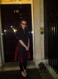 Me in front of the black door of 10 Downing street in a red polka dot tee dress with a black shawl.