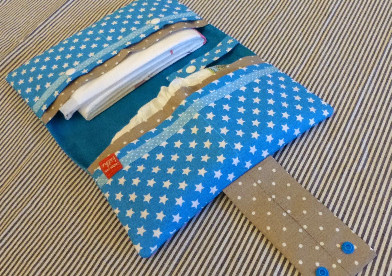 aufgeklappte Windeltasche befüllt mit Windeln, Wickelunterlage und Feuchttücher, die Nuckelkette verhindert das verlieren des Nuckels
