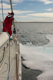 Mirek pushing an ice floe from our bow and anchorchain in Paisley Bay
