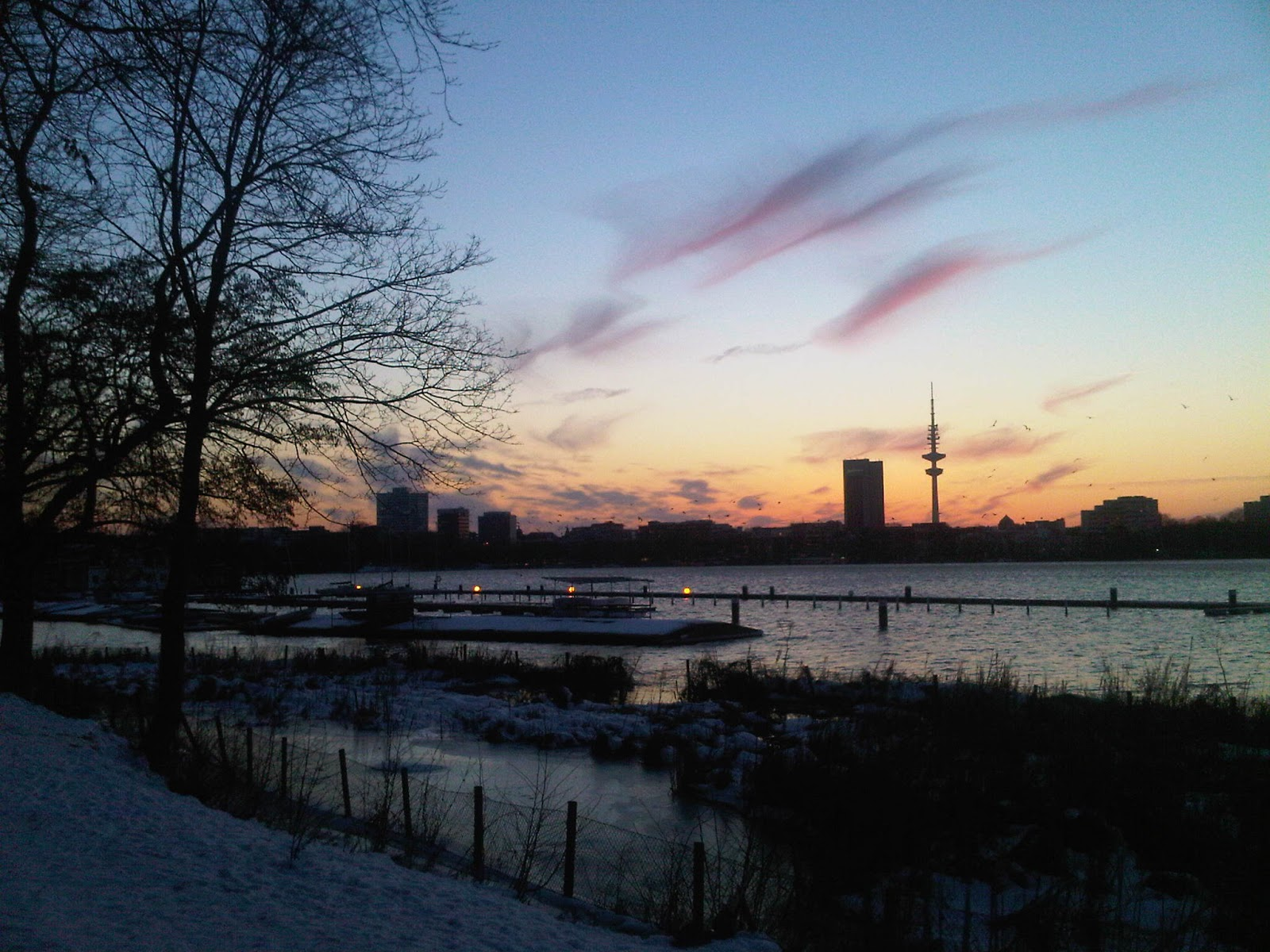 Silhuette vom Fernsehturm in Hamburg über die Alster bei Sonnenuntergang. Steg, Lampen über dem Wasser.