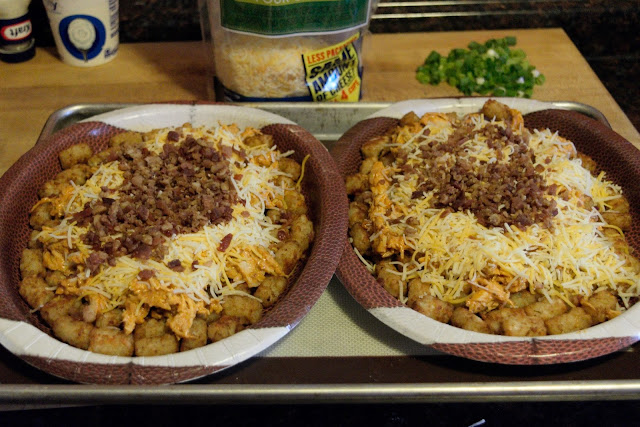 The two football plates, on a baking sheet, filled with tater tots, chicken mixture, shredded cheese, and topped with real bacon bits.