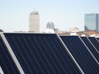 Roof Mounted Solar Thermal Panels with the Boston Skyline Behind Them