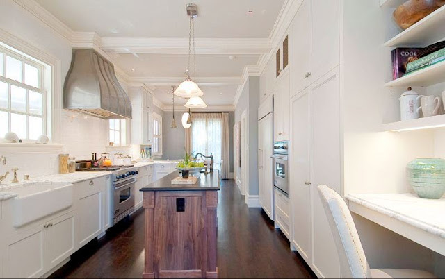 Kitchen with white cabinets, wood stained island, pendant lights and dark wood floor
