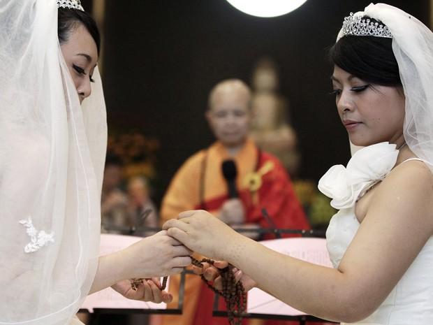 You Ya-ting (à esquerda) e Huang Mei-yu fazem oração durante cerimônia simbólica de casamento budista de pessoas do mesmo sexo em um templo em Taoyuan, no nordeste de Taiwan. O casal de lésbicas, de 30 anos, se casou depois de namorar por sete anos neste (Foto: Reuters)
