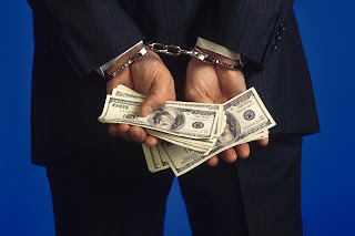 Photo of handcuffed man with money in his hands.