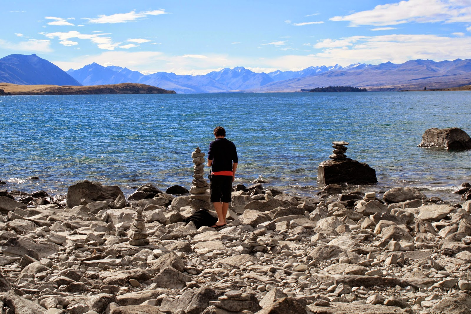 Jesse standing next to a pile of stacked stones by Lake Tekapo, in the South Island of New Zealand.