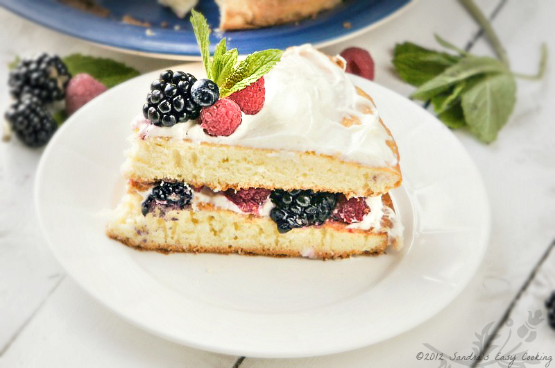 Homemade Summer or Spring Berry Bursting Cake. Delicious and with loads of fresh mixed juicy berries.