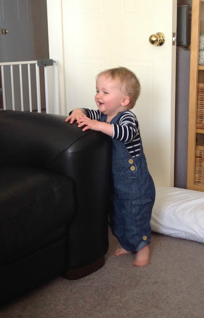baby stood by sofa laughing