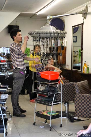 A woman with her hair in rollers and a crazy gadget at the hairdressers photograph