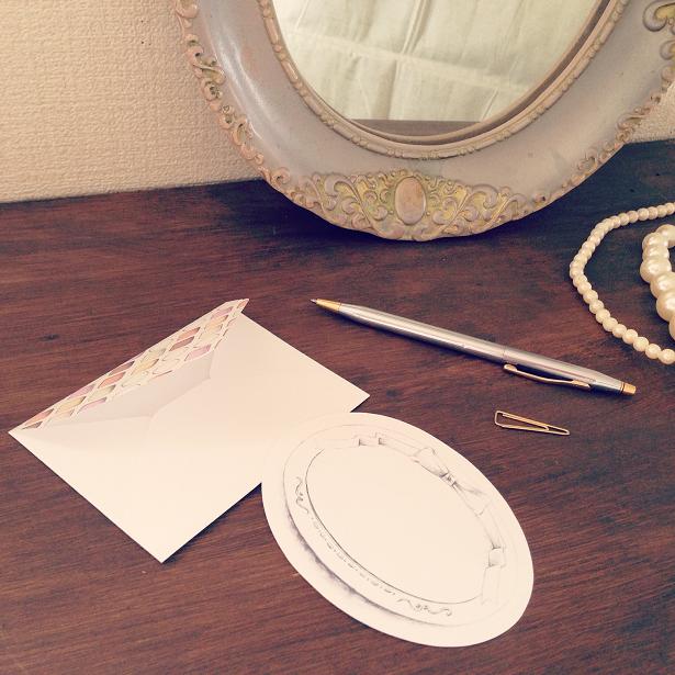 レターセットやアンティークの鏡、ネックレス、ボールペンなどが机の上に並べられた様子。