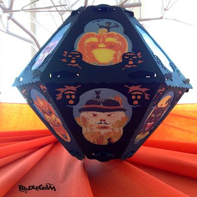 View of the pumpkin and scarecrow on vintage-style Bindlegrim Halloween paper lantern floating over a sea of vintage orange crepe.