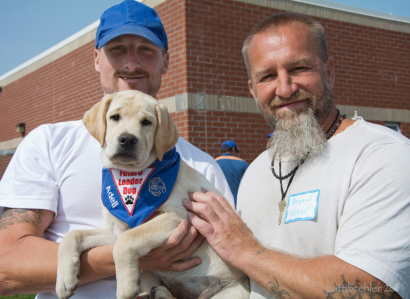 "Two men are standing in front of a brick building looking at the camera and smiling. They are wearing white t-shirts. The man on the left has a blue baseball cap on his head and is cradling a small yellow lab puppy in his arms. The man on the right is resting his left hand on the puppy's side. The puppy's front legs are hanging over the man on the left's right forearm. The puppy is looking at the camera and is wearing the blue Future Leader Dog bandana with the name ""Adell"" embroidered in white."