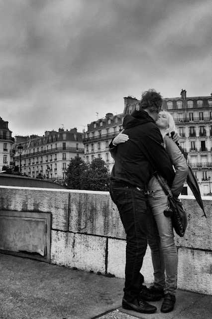 A man and a woman kiss near the hotel de la ville in Paris in this street photograph