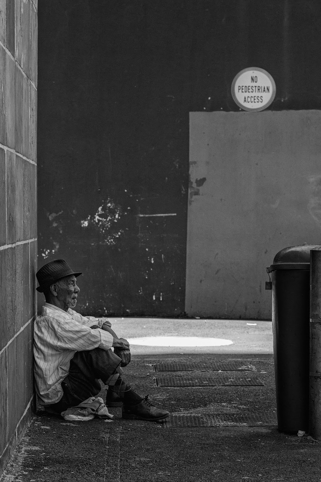 A man sits against a wall- his hat, a manhole cover and a road sign are all circles.