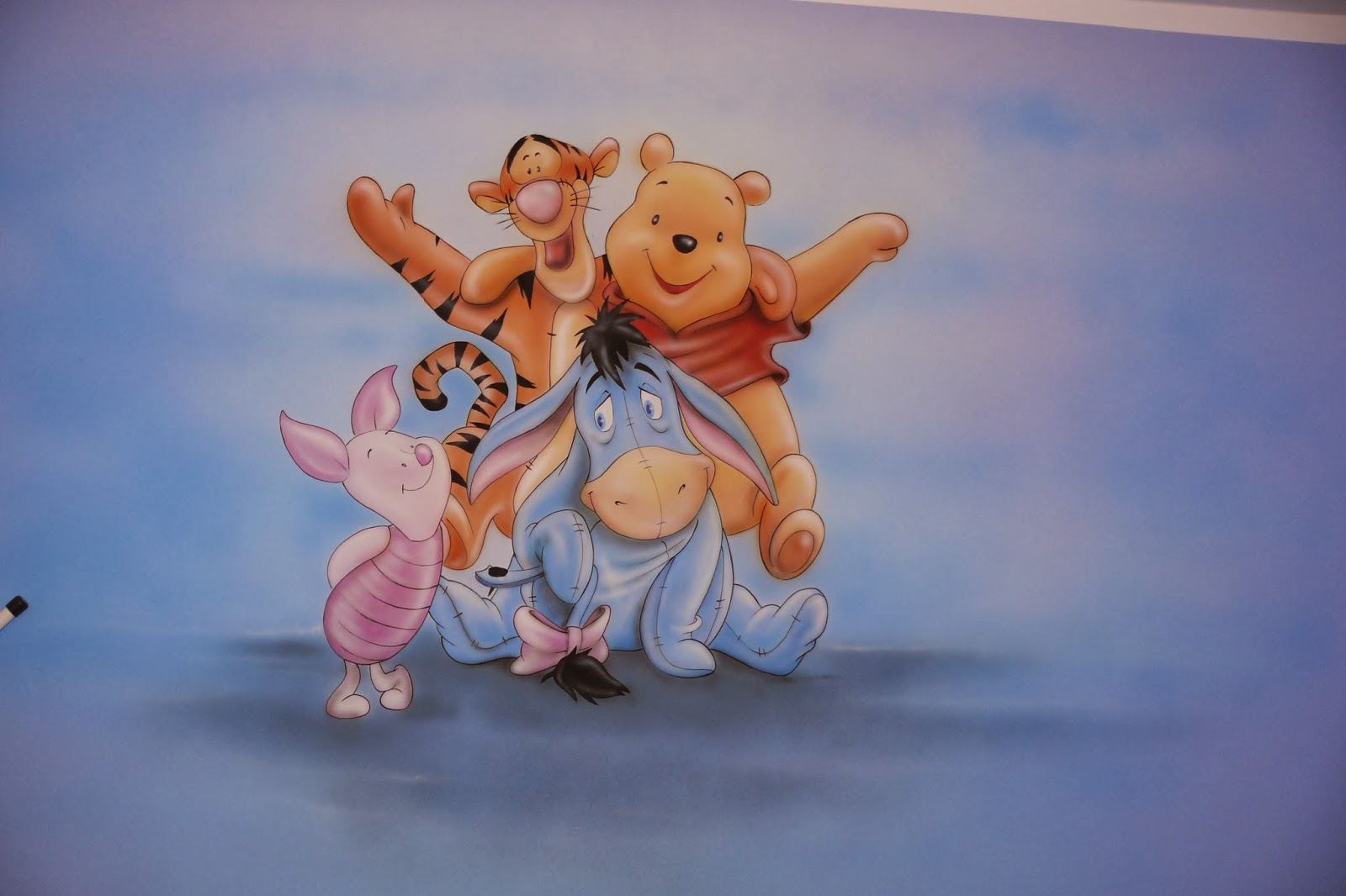 Artystyczne malowanie ściany, motyw przedstawia Kubusia Puchatka, obraz namalowany na ścianie w pokoju dziecka