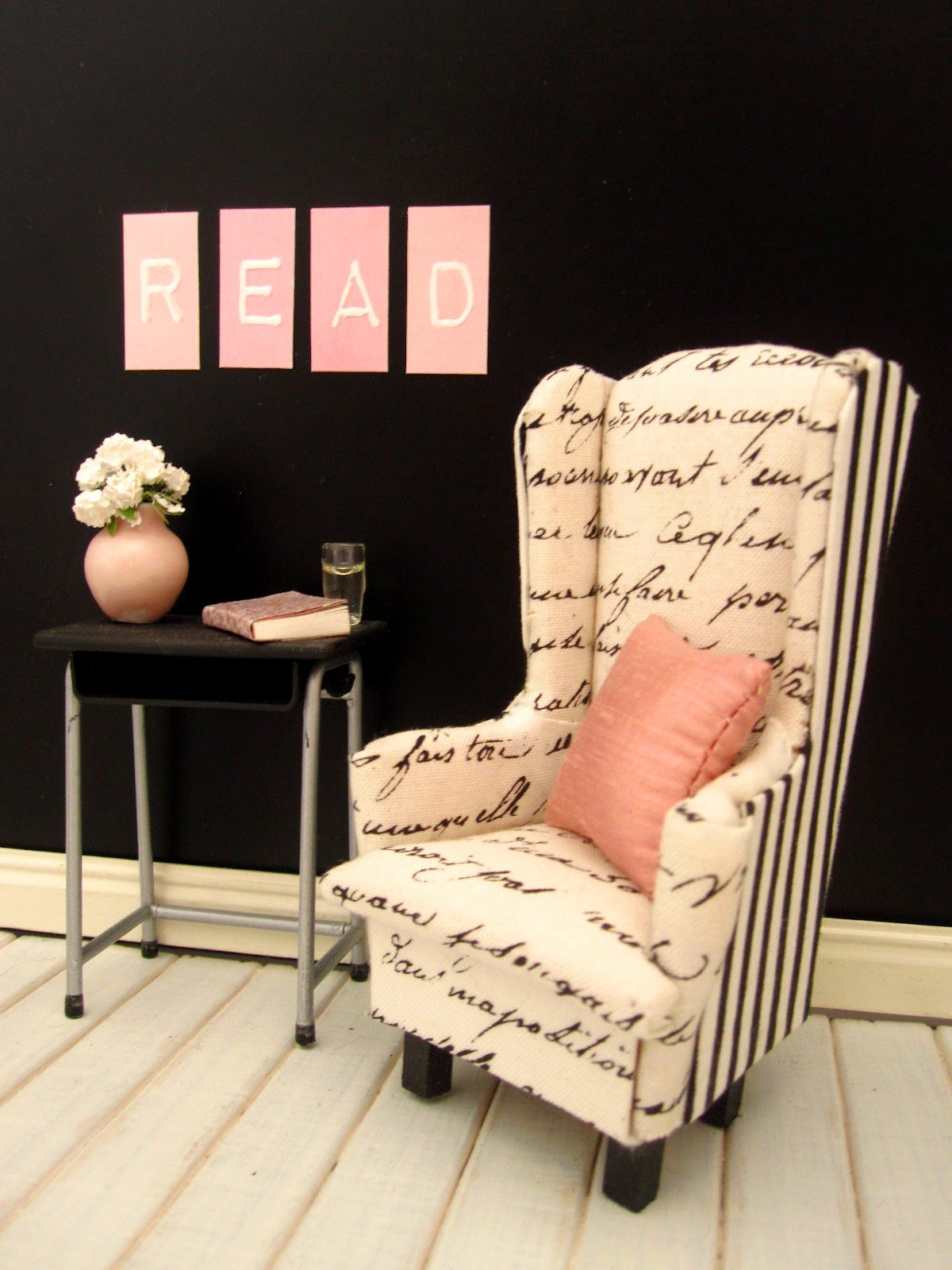 Modern doll's house miniature scene of a black and white wing chair against a black wall. On the wall are the letters R,E,A and D in pink and white and on the table under them is a pink vase, book and a glass of water.