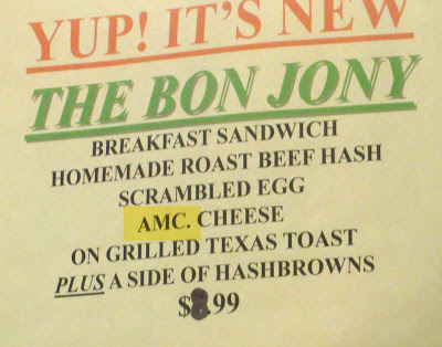 Close up of a sign that mentions AMC. CHEESE on a breakfast sandwich