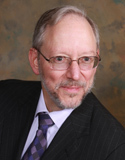 A professional headshot of a middle-aged man with a neatly trimmed beard and eyeglasses