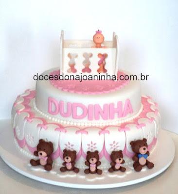 Bolo para chá de bebê decorado com bercinho e bebê em tons de rosa e ursinhos marrom.