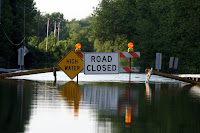 """Road Closed"" sign on flooded street"