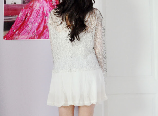 The back of the lace shift dress from SheInside/SheIn, with its detailed lace design and white crepe hem.