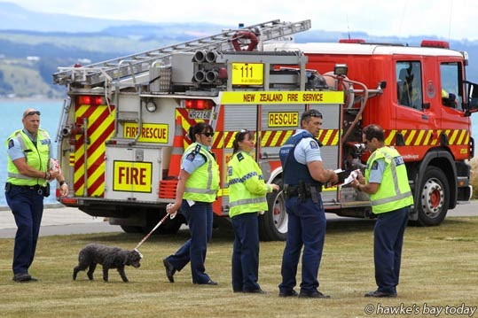 Police led away a dog tied onto a length of emergency tape, after Police, Napier Fire Service and St John Ambulance staff removed a woman's body from the breakwater by the boardwalk along the entrance to the Inner Harbour, along Nelson Quay, near Perfume Point, Napier. photograph