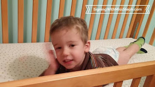 32 month old lying on stomach in new bed signs BED