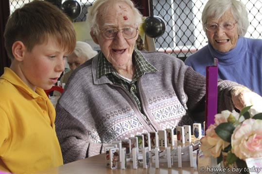 L-R: Tyler Harford, Douglas Barrett, resident, Jean Barrett, visitor, sister - pupils from Mahora School, Hastings, playing domino-based activities with residents of Gracelands Lifestyle Care and Village, Hastings. photograph