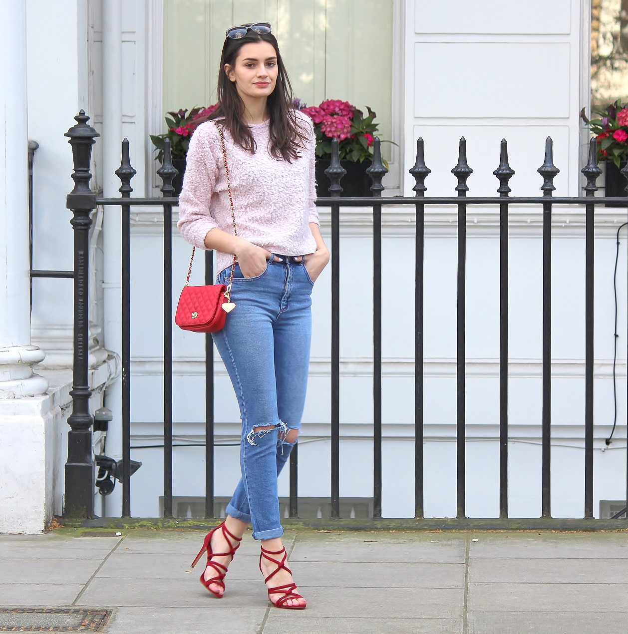 peexo fashion blogger wearing pink fluffy jumper and ripped mom jeans and red strappy heels and red small bag in spring