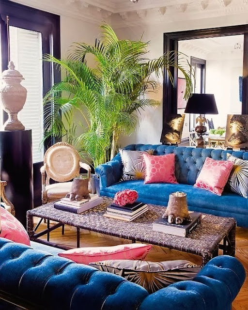 pink cushions on a midnight blue chesterfield sofa