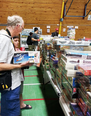 A man and a boy choosing model kits at a scale model show.