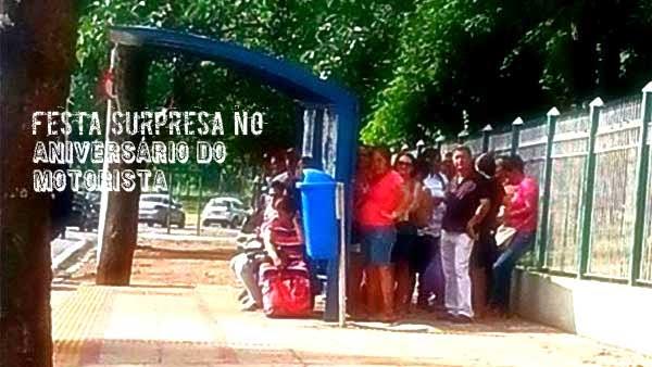 Na imagem, várias pessoas estão atrás do ponto de ônibus, se escondendo dos raios solares.
