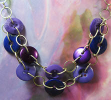 Plunging double strand necklace has purple and blue buttons linked with silver chain