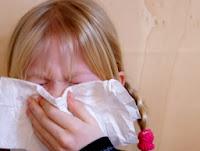 Kind putzt sich die Nase mit Taschentuch