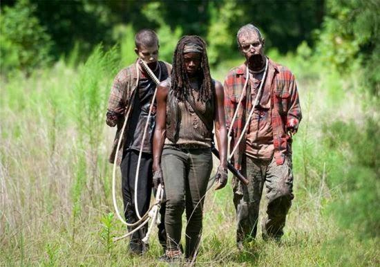 Michonne, escoltada por dos zombies, deambula por los caminos