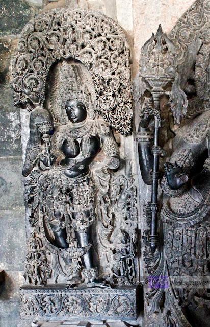 Female attendant behind the Dwarapalaka on the left side of the Hoysaleshwara shrine