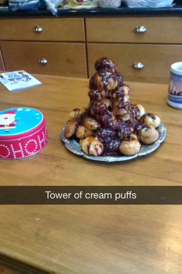 this is a plate of cream puffs covered in chocolate arranged in a tower on a wooden table