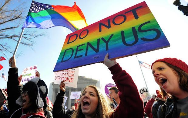Manifestantes pró casamento entre pessoas do mesmo sexo carregam cartaz escrito 'não nos neguem' durante protesto em frente à Suprema Corte dos EUA (Foto: Jewel Samad/AFP)