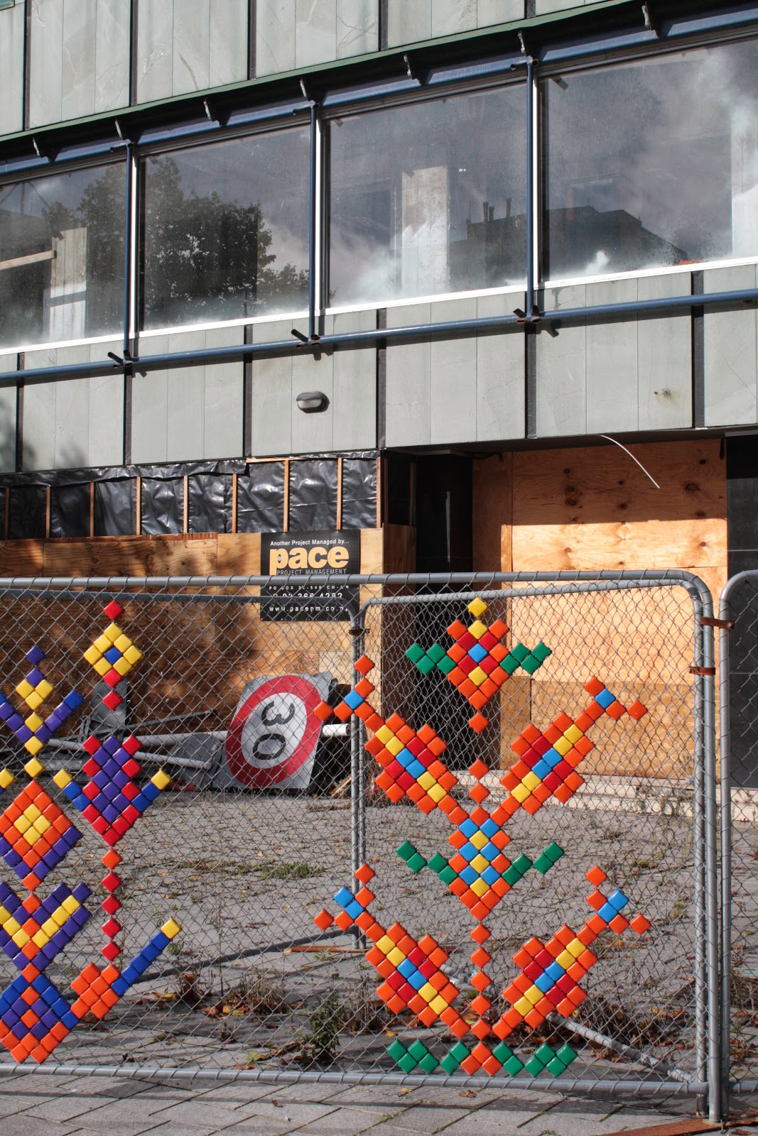 Plastic thingies stuck into hurricane fencing in the shape of flowers in front of a boarded up building.