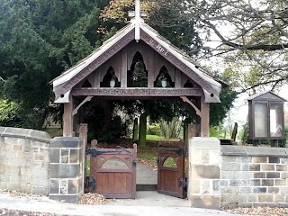 A wooden double gate set in a stone wall with an gabled structure above.  Decoratively carved and with shaped fretwork.  Surmounted by a wooden cross.