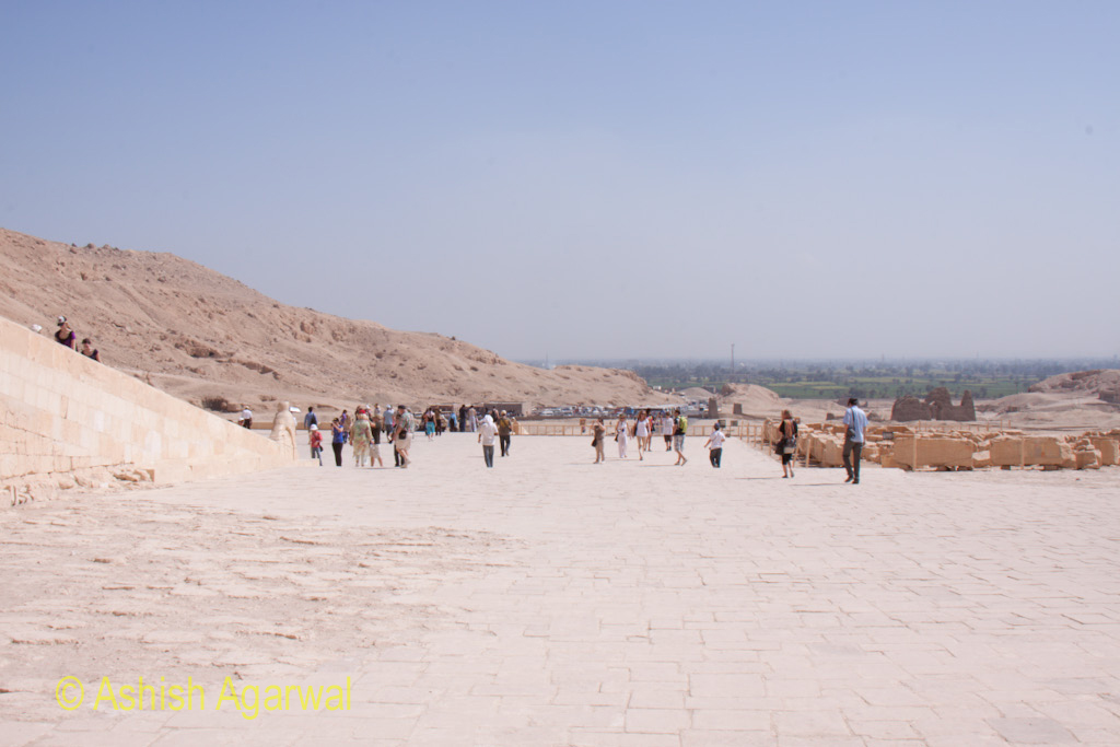 Tourists walking near the ramp that takes people to the higher levels of the Queen Hatshepsut mortuary temple near Luxor in Egypt
