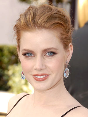 Amy Adams sweeps her tousled hair back into a messy bun.