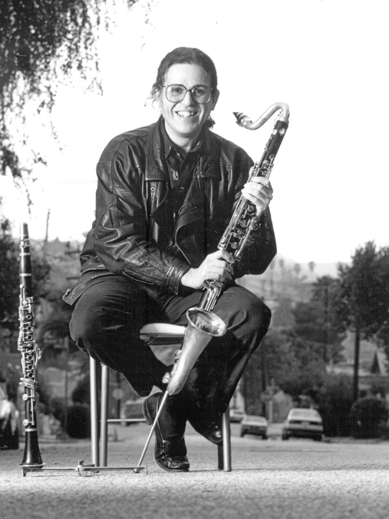 David Ocker sitting in the middle of a street with bass clarinet, early 1990s