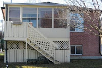 image Kawartha Lakes Home for Sale showing sunroom with stairs leading into fenced back yard