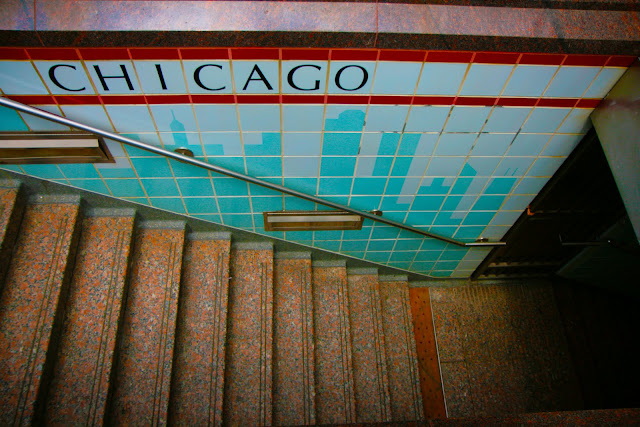 A skyline mural made of tiles by the staircase down into a train station in Chicago.