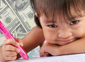 photo image of a toddlers holding a pink pen with hundred dollars in the background.