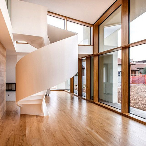 helicoidal staircase is a sculptural focal point within casa PLS by Corde Architetti Associati